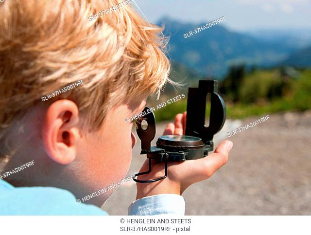 Boy using compass outdoors