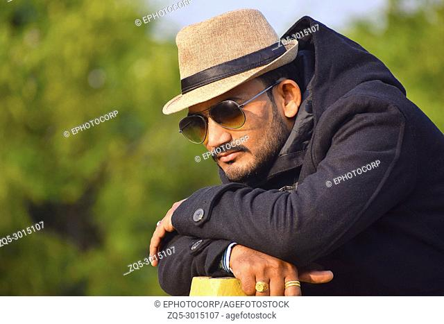 Man in a hat and black jacket in thinking pose, Pune, Maharashtra