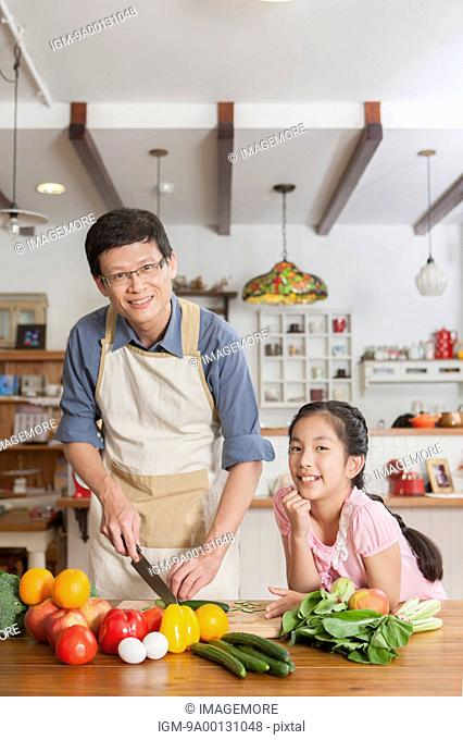 Father and daughter cooking together in kitchen