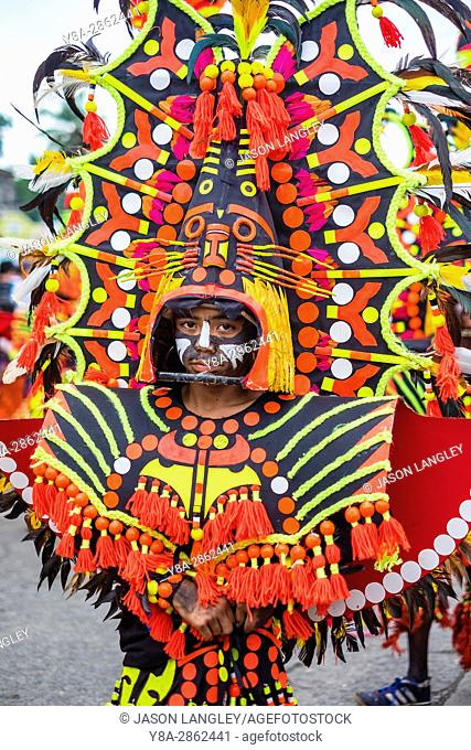 Kalibo, Aklan, Western Visayas, Philippines. A participant in the Ati-atihan festival wearing brighly-colored hand made costume made from recycled and natural...