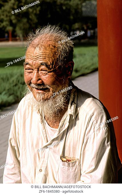 Colorful portrait of elderly Chinese man with beard in Beijing China