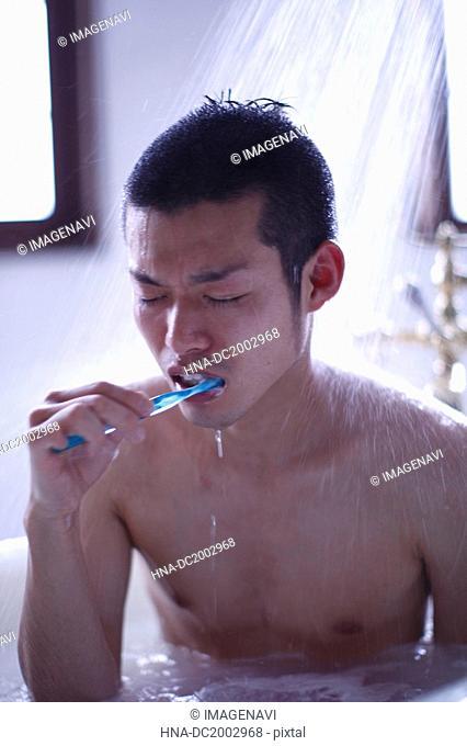 Man Who Sitting Under Shower Brushing His Teeth