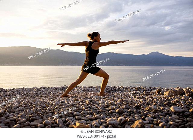 Young woman doing yoga at the stony beach in the evening, Warrior pose