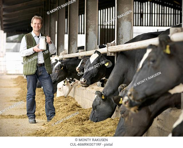 Farmer holding jug of milk by barn