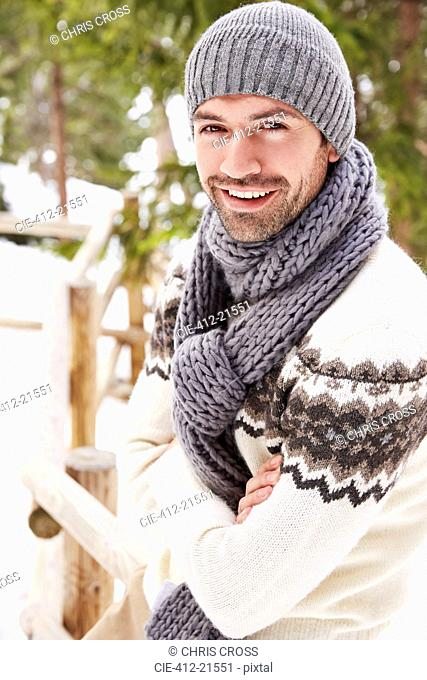 Smiling man sitting on snowy fence