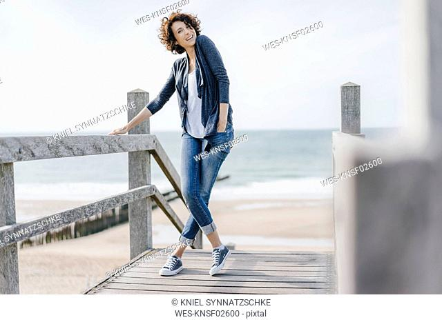 Portrait of smiling woman standing on boardwalk at the beach