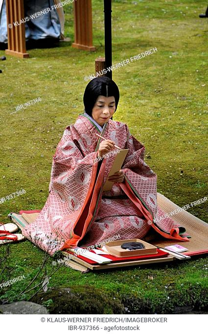 Japanese woman in a kimono of the Heian period writing with a brush whilst sitting down during a Shinto ceremony in the Kamigamo Shrine in Kyoto, Japan, Asia