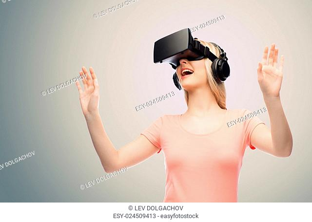 technology, virtual reality, entertainment and people concept - happy young woman with virtual reality headset or 3d glasses and headphones playing game over...