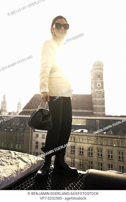 fashionable blogger woman on balcony next to church Frauenkirche, Marienkirche in city Munich, Bavaria, Germany