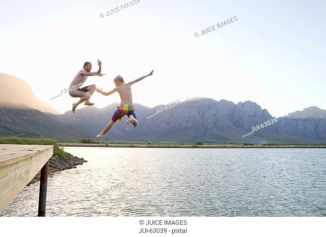 Father and son jumping into lake from jetty