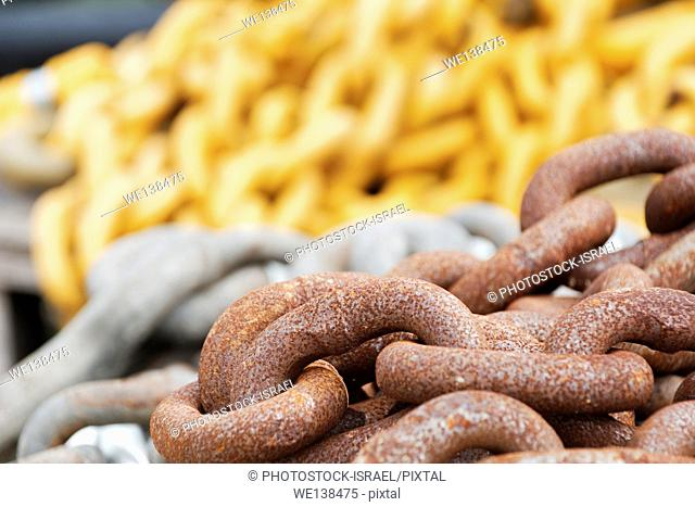 three different chains selected focus on the foreground rusty chain