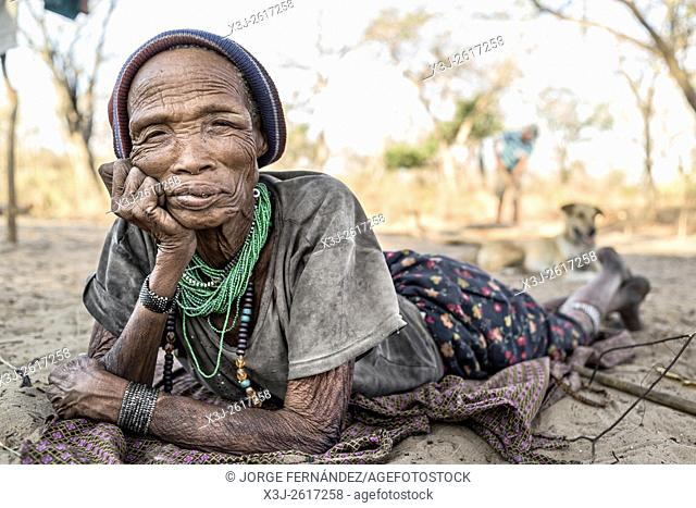 Portrait of a woman from the San tribe lying on the sandy floor of her village in a remote part of the Kalahari desert