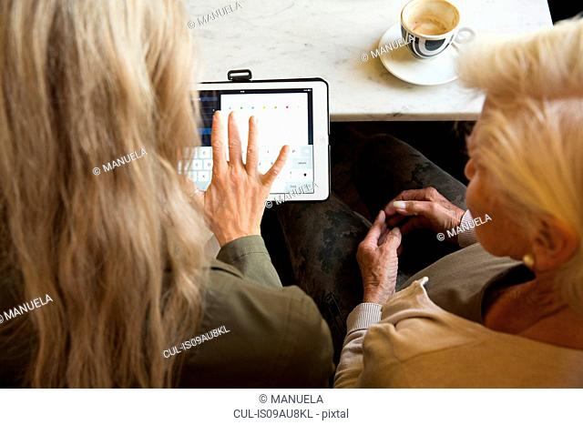 Mother and daughter sitting together in cafe, looking at digital tablet, rear view