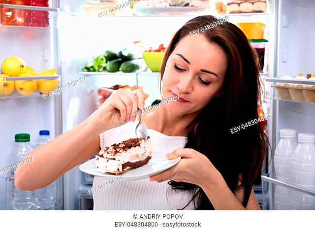 Close-up Of A Woman Eating Cake Near Open Refrigerator