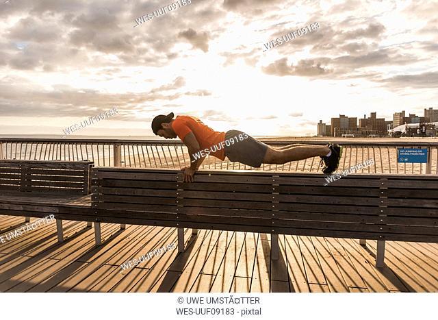 USA, New York City, man exercising on Coney Island