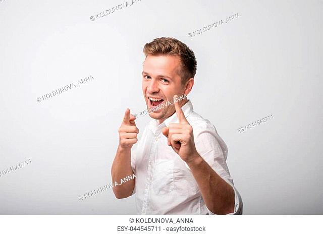 Happy caucasian man standing and smiling. Beautiful male half-length portrait. He is happy and lucky of winning something