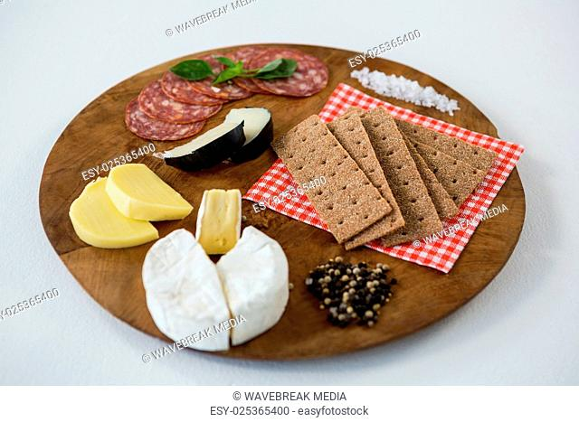 Variety of cheese with salami, crackers, spices and sea salt on wooden board