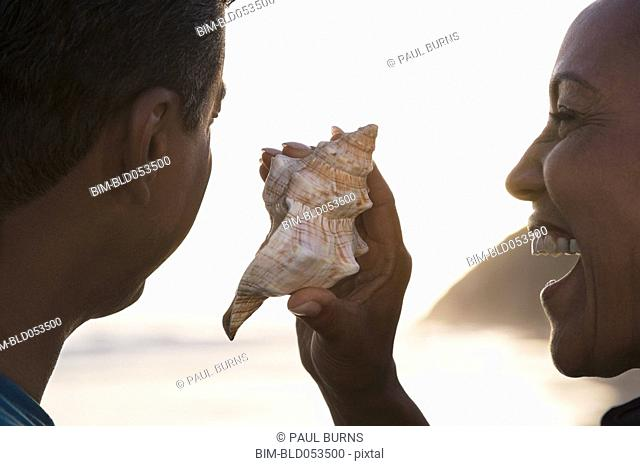 Mixed Race woman holding seashell next to husband