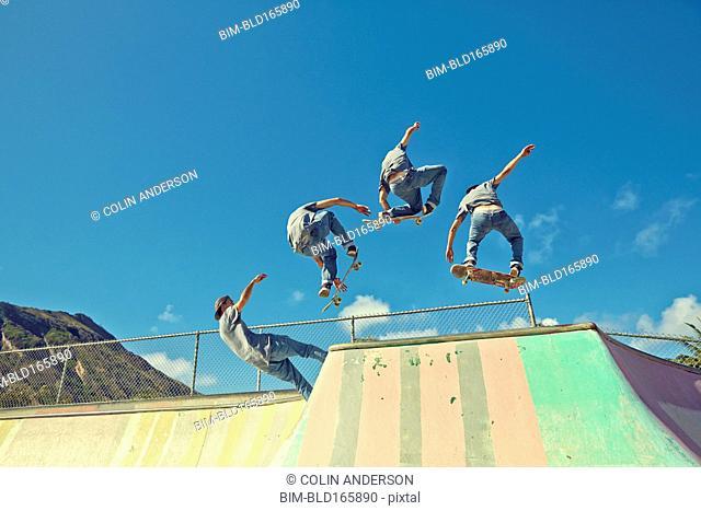 Multiple exposure of Caucasian man performing trick at skate park