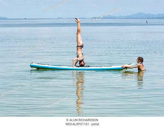 Thailand, Krabi, Lao Liang, woman doing a headstand on SUP Board in the ocean