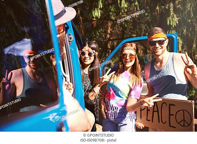 Young boho hitchhikers with peace sign by recreational van