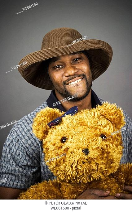 Young black man wearing a hat and holding a stuffed animal