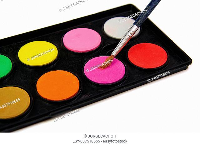 Watercolor paint and brush in black box on white background