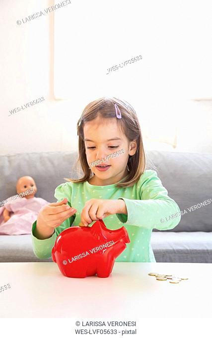 Girl putting coin into piggy bank