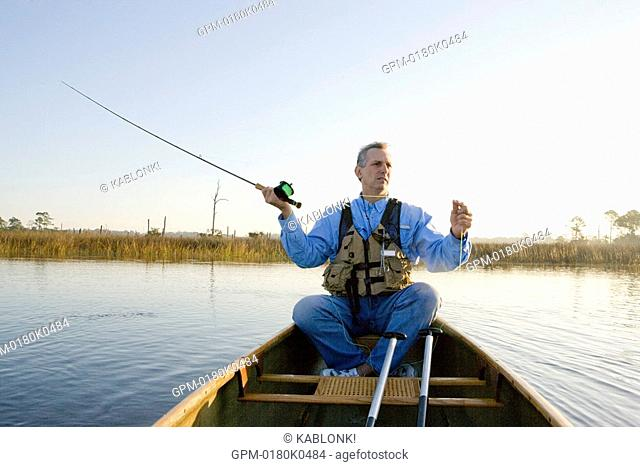 Mature adult man fishing in canoe on river and casting reel