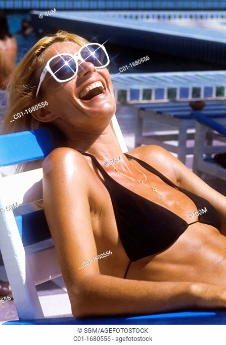 Laughing woman with sunglasses and black swimsuit