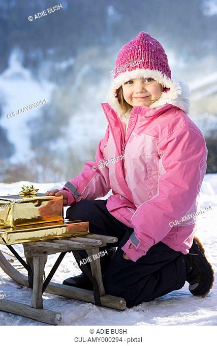 Portrait of girl with presents on sledge