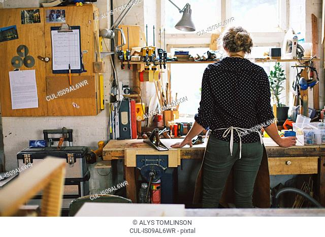 Rear view of young craftswoman at workbench in pipe organ workshop