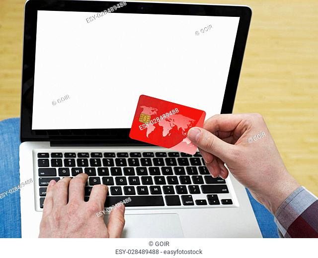 Man at home, shopping online from a laptop with a credit card,Map: http://www.lib.utexas.edu/maps/world.html