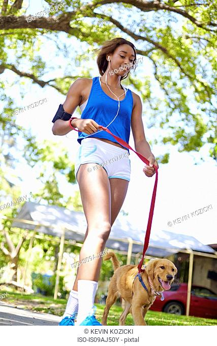 Young woman exercising with dog in park