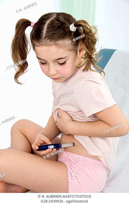 Little girl with bunches suffering from diabetes injecting herself insulin