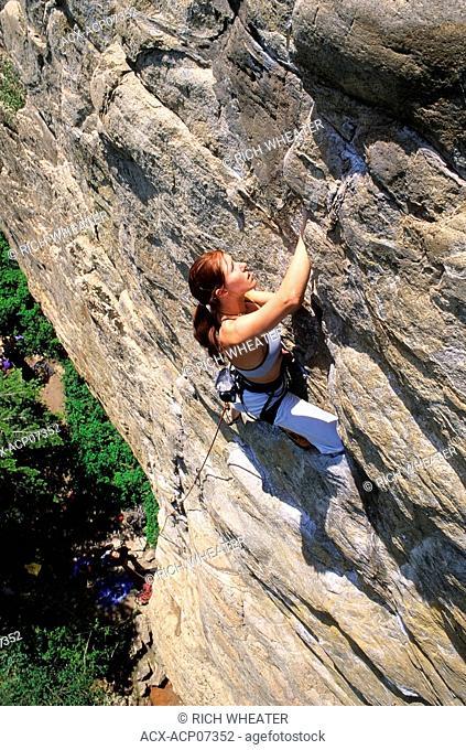 Female rock climber on Minor Skirmish, 5.10b, the Fortress, Skaha Bluffs. Penticton, British Columbia, Canada
