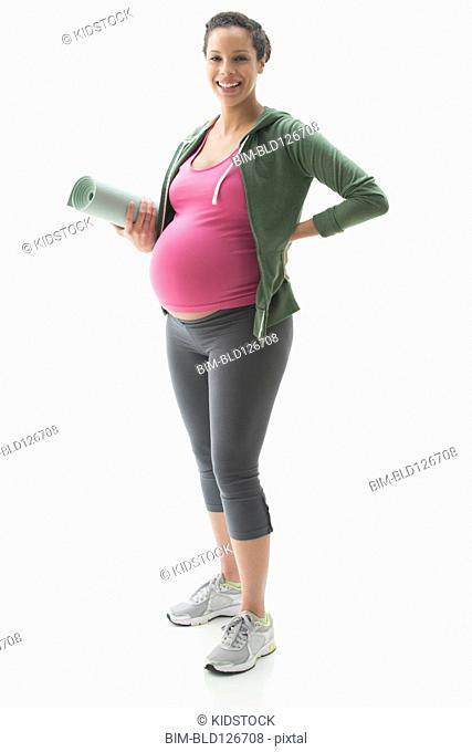 Portrait of pregnant mixed race woman with yoga mat
