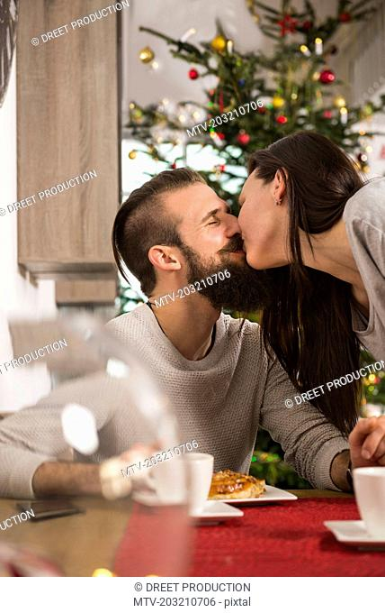 Couple kissing at breakfast table
