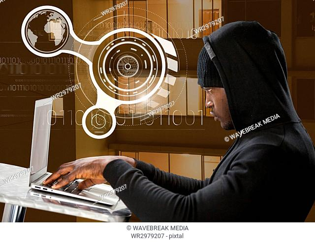 Side view of hacker using a laptop in front building