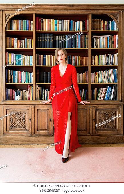 Tilburg, Netherlands. Woman in Red inside her vintage reading room library