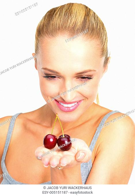 Positive young woman looking at two black cherries in her hand