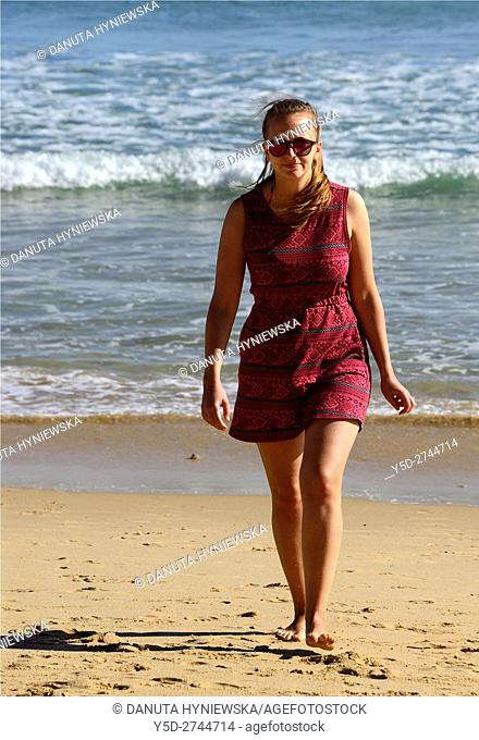 young woman enjoying vacation on the beach, here free of crowds Porto de Mos beach, Lagos, Algarve, Portugal, Europe