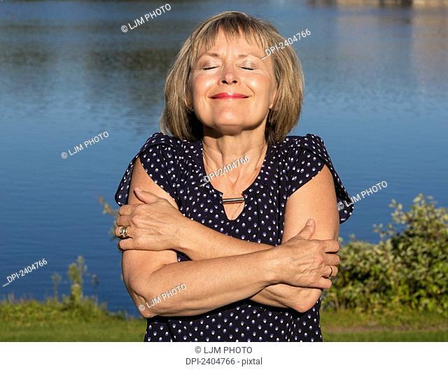 Mature woman relaxing in Hawrelak Park; Edmonton, Alberta, Canada