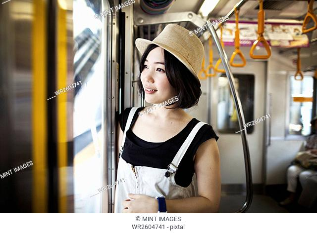 Young woman wearing a hat traveling on a train
