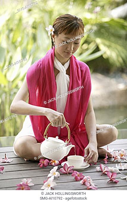 Young woman pouring tea, portrait