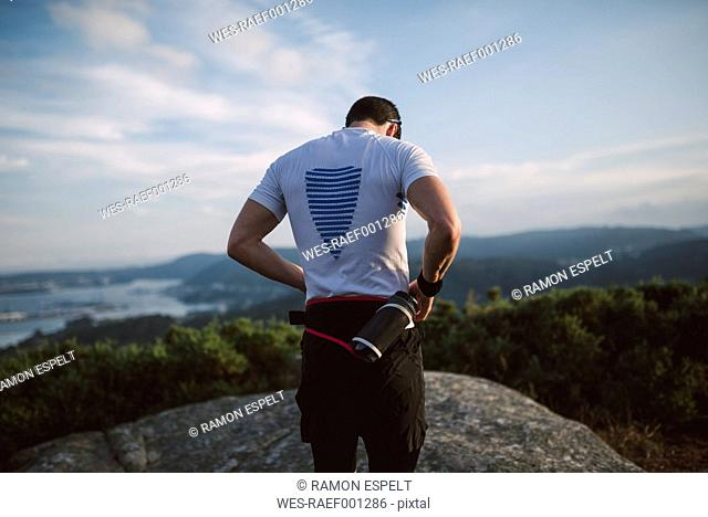 Trail runner, man standing on rock