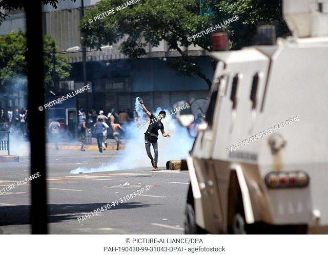30 April 2019, Venezuela, Caracas: A demonstrator throws a tear-gas grenade against security forces in clashes in the capital