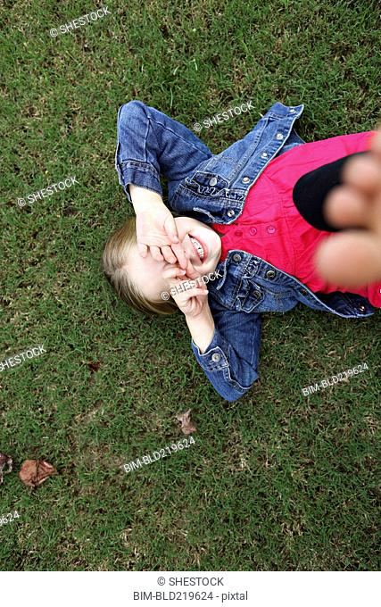 High angle view of girl laying in grass