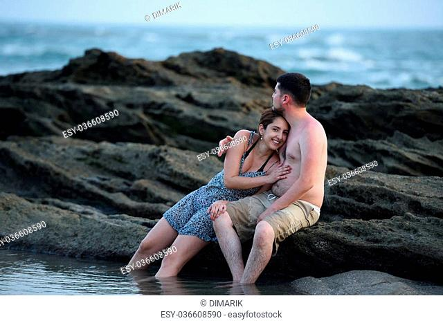 Couple sitting on a rock in the beach