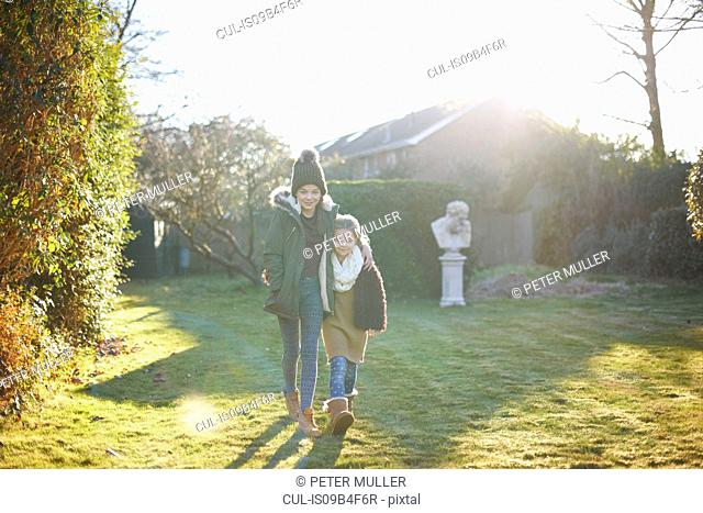 Siblings enjoying sun in garden